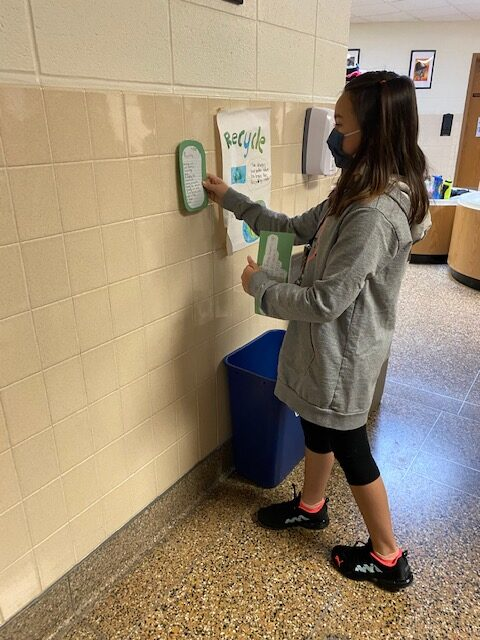 Student places her poem on recycling by the recycling bin.